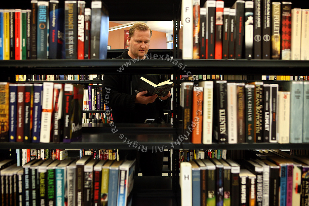 An inmate is taking a look at a book while working in the prison library, containing not only books but also magazines, CDs and DVDs, inside the luxurious Halden Fengsel, (prison) near Oslo, Norway.