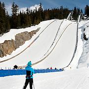 A jumper walks past the ski jumps 2017 CDN National Championships.  Sunday, April 2, 2017.  <br /> <br /> Photo:  David Buzzard
