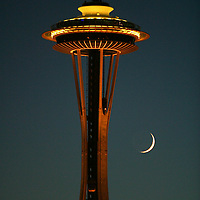 The Crescent moon dips below the Space Needle in Seattle.