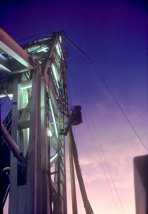Roughneck climbing oil rig against a pink and dark blue dusk sky, Webster, Texas.