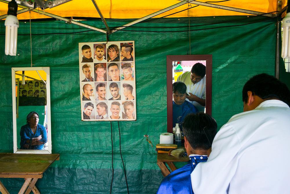 """FEIRA DA KANTUTA - Diversos """"peluqueros, estilistas e barberos"""" (cabeleireiros) trabalham em barracas da feira boliviana na praça Kantuka, no bairro Canindé, em São Paulo. Rolando Ticona, 42 anos, é de Santa Cruz de La Sierra (cidade na fronteira da Bolívia com o Brasil), está no Brasil há 9 anos trabalhando como cabeleireiro.  Seu cliente nesta foto é Nelson Juanequino, tem 39 anos e veio de Ururo - Bolívia, há 20 anos, com sua mulher Virgínia Sanches, de 41 anos, natural da capital boliviana La Paz (ela aparece no espelho). 19/06/2016"""