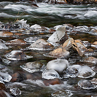 WA08998-00...WASHINGTON - Ice rimed rocks in the South Fork Snoqualmie River near Olallie State Park.