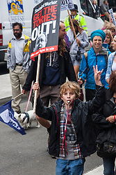 London, July 10th 2014. A child supports his parents as thousands of striking teachers, government workers and firefighters march  through London in protest against cuts and working conditions.