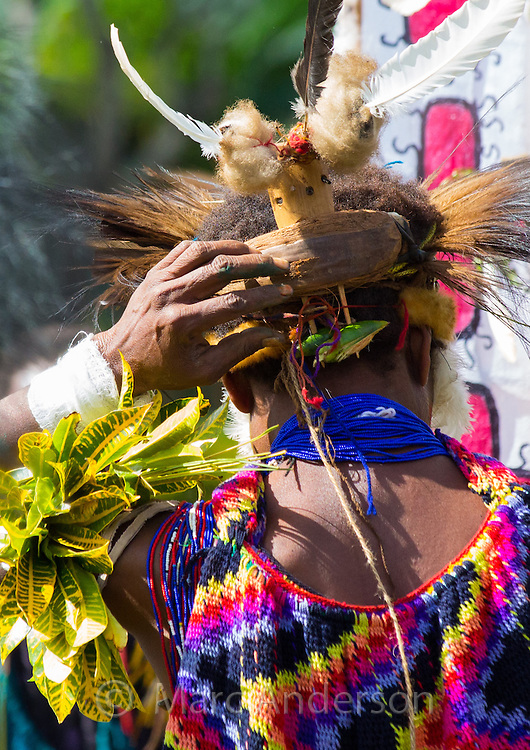 Rear view of a tribeswoman wearing traditional dress at the Goroka Show in papua New Guinea. She is carring a colourful bilum bag on her head and her headdress is adorned with birds feathers and a small wooden crown.