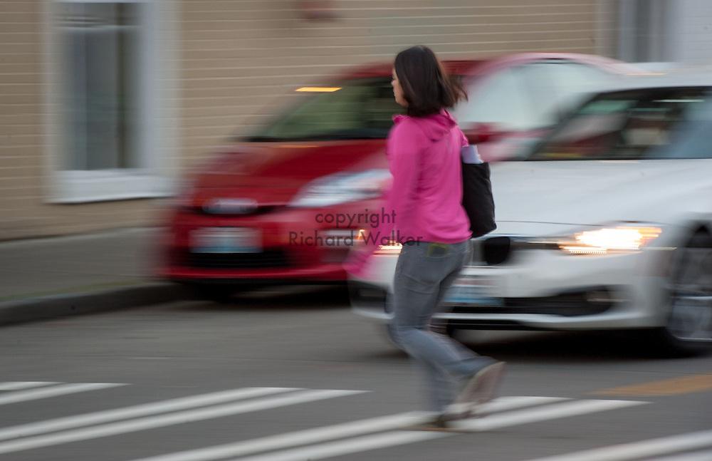 2016 October 10 - A pedestrian crosses a street in the University District, Seattle, WA, USA. By Richard Walker