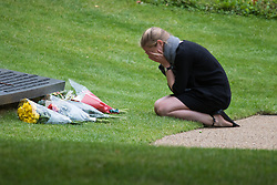 Hyde Park, London, July 7th 2015. As Londoners remember the tenth anniversary of the 7/7 bombings, a woman is overcome with emotion as she lays  flowers at the memorial in Hyde Park.