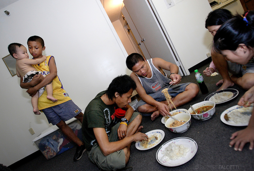 Lay Moo holds fellow refugee Na Le Htoo, the child of Ya Za and Ku Ku while the others ate a meal. Eating sitting from left, his brother Ler Bwey, Ya Za, Htee Shee Paw and Ku Ku eat dinner on the floor of Ya Za's apartment October 4, 2007..(Photo by Robert Falcetti)