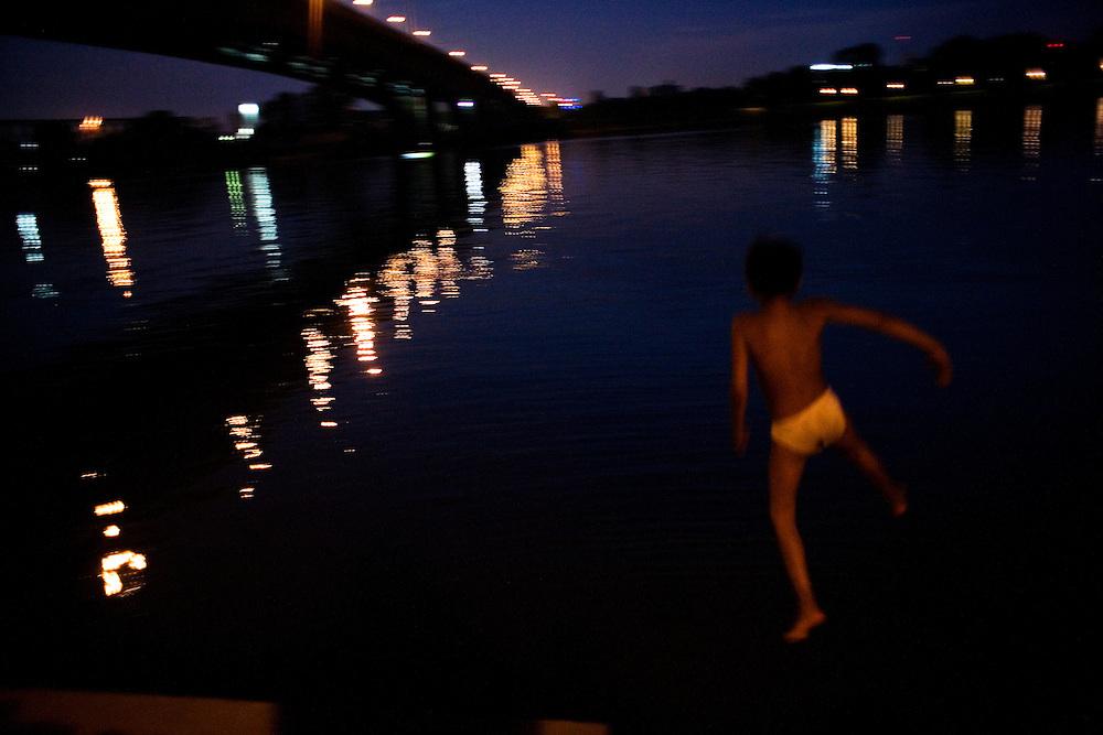 Boys from the Stara Gazela camp swim in the Sava River at dusk near the Gazela Bridge.
