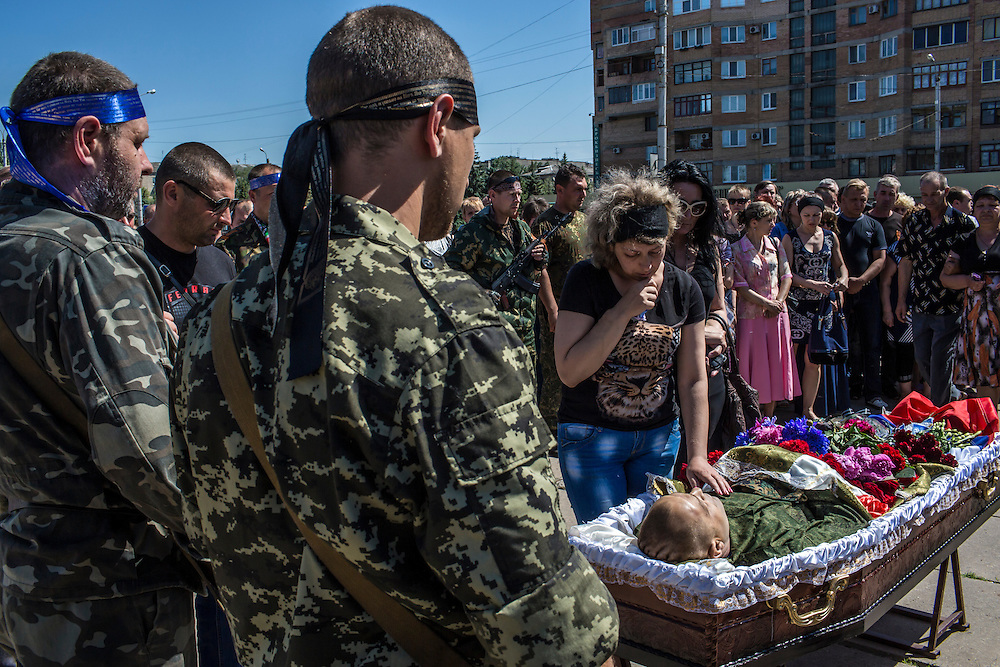HORLIVKA, UKRAINE - MAY 24: Friends and relatives grieve over the body of Aleksandr Politov, a pro-Russia militia fighter who was killed when his group attacked a Ukrainian military checkpoint two days earlier in the village of Blahodatne, outside the occupied city administration building on May 24, 2014 in Horlivka, Ukraine. Presidential elections are scheduled for tomorrow, but pro-Russia militias have been seeking to prevent them from being administered throughout the eastern part of the country. (Photo by Brendan Hoffman/Getty Images) *** Local Caption ***