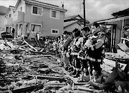 Rescue workers pause from work for a collective prayer for the dead a week after the precise moment the tsunami struck Ofunato, Iwate Prefecture, Japan.  The number of missing or dead has topped 26,000 and the confirmed death toll has risen to over 10,000 people.