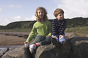 boy and girl sitting on a rock enjoying the view