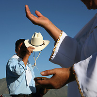 A man looks on as a healer and follower of Nino Fidencio, a curandero or healer who passed away in the 1938, conducts a healing session on top of a hill just outside of Espinazo, Mexico on October 18, 2006. Followers of Nino Fidencio believe that his spirit can posses other healers, who once possessed speak in a child like voice and perform a variety of medical cures on their followers. His believers, an estimated 20,000, gather in his hometown for a three-day festival twice a year in March and October. (Photo/Scott Dalton)