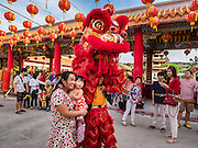28 JANUARY 2017 - SAMUT PRAKAN, SAMUT PRAKAN, THAILAND: Lion dancers pose for photos with people before the Chinese New Year Lantern Festival at the Tham Katanyu Foundation shrine in Samut Prakan, a suburb about 15 miles from Bangkok. More than 5,000 handmade lanterns imported from Taiwan are hung on the grounds of the shrine. Some of the lanterns are traditional Chinese lanterns, others are in the shapes of people or deities. There is also traditional Chinese entertainment, likes lion dances, at the festival.     PHOTO BY JACK KURTZ