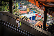 2015/11/20- Medellín, Colombia: A boy goes down the electric staircase in Barrio Las Independencias in Comuna 13, Medellín. The Comuna 13 was once one of the most violent of Medellín. Nowadays many tourists come to visit to see its famous street art and the iconic electric stairscases that facilitate the mobility of the residents up and down the hill. Life in Medellín is changing quickly. Once consider the murder capital of the world is now being revitalized by enormous urbanism projects. (Eduardo Leal)