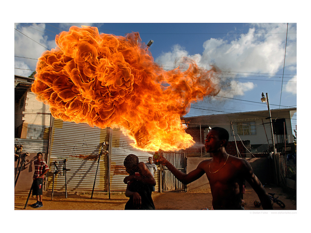 """A member of the Keylemanjahro School of Arts and Culture in Cocorite, Trinidad, practices his fire blowing skills...Prints available in 3 sizes:.20""""x30""""   90.00 $ .24""""x36"""" 150.00 $.30""""x40"""" 180.00 $.personal download: 45 $ and 90 $. .Click 'buy print' and choose your size...Different sizes or comments: stefanfalke@mac.com"""