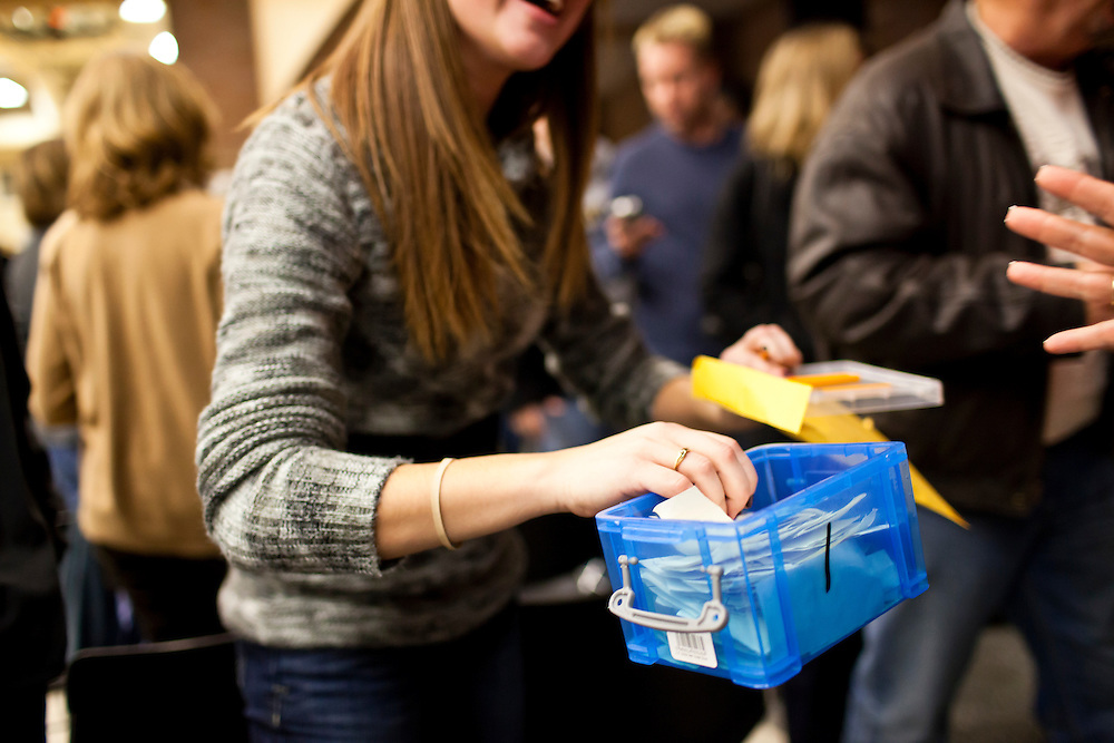 A poll worker collects ballots at a caucus site at Summit Middle School on Tuesday, January 3, 2012 in Johnston, IA.