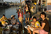 Family working at Ampawa floating market. They make the most delicious assortment of foods sold to visitors to this very popular market. Samuthsongkram province