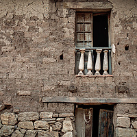 An old mud brick home showing a window and part of a door.