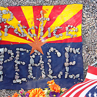 """An Arizona and U.S. flag with stones spelling """"practice peace"""" is seen at the memorial outside the offices of congresswoman Gabrielle Giffords in Tucson, Arizona January 11, 2011. REUTERS/Rick Wilking (UNITED STATES)"""