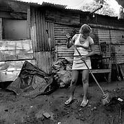 "May 15, 2005 - Managua, Nicaragua - Meiling, 15, a prositute does her chores at her home. Meiling has four siblings and her father left 3 years ago. ""Mother tried to find odd jobs but a friend of mine came to me and told me about working on the highway."".    ""I'm in the 4th grade and I use the money sometimes to buy my notebooks. I go to the afternoon school shift."" .     ""We'd all be starving and i'd rather do what  I do than see my siblings go hungry.""."