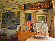 """Montana's oldest standing public school, used in the town of Twin Bridges from 1867-1873, is now preserved at Nevada City, Montana, USA. The wooden classroom contains a desk, old books, chalkboard, an American flag with 48 stars, a bust of President Lincoln, a bird cage, and chairs. Nevada City was a booming placer gold mining camp from 1863-1876, but quickly declined into a virtual ghost town. This fascinating town inspires you to imagination what life must have been like in early Montana when gold was discovered at nearby Alder Gulch. More than 90 buildings from across Montana have been gathered for preservation at Nevada City, mostly owned by the people of the State of Montana, and managed by the Montana Heritage Commission. In 2001, the excellent PBS television series """"Frontier House"""" used one of the buildings and its furnishings to train families in re-creating pioneer life. A miner's court trial and hanging of George Ives in the main street of Nevada City was the catalyst for forming the Vigilantes, a group of citizens famous for taking justice into their own hands in 1863-1864. Directions: go 27 miles southeast of Twin Bridges, Montana on Highway 287."""