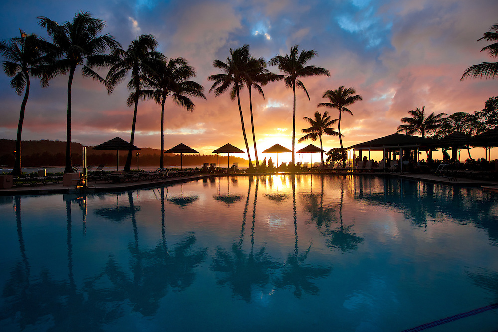 Umbrellas, lounge chairs and palm trees surround the oceanside swimming pool at the Turtle Bay Resort on the North Shore of Oahu, Hawaii