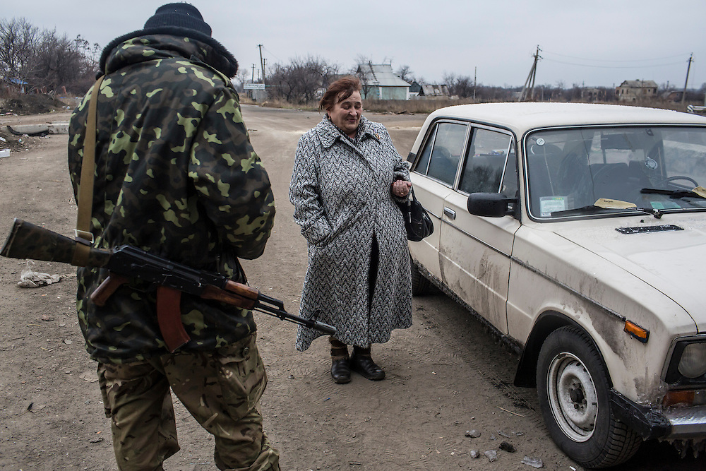 PERVOMAISKE, UKRAINE - NOVEMBER 18, 2014: A woman traveling with her husband to their home in the town of Ilovaisk attempts to pass a checkpoint guarded by the 5th platoon of the Dnipro-1 brigade, a pro-Ukraine militia, in Pervomaiske, Ukraine. CREDIT: Brendan Hoffman for The New York Times