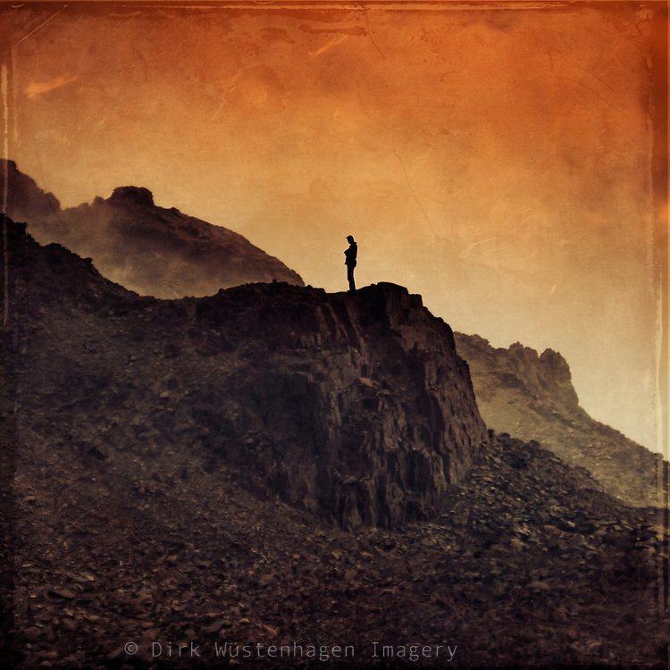 Man standing on a mountain under a red sky - manipulated photograph