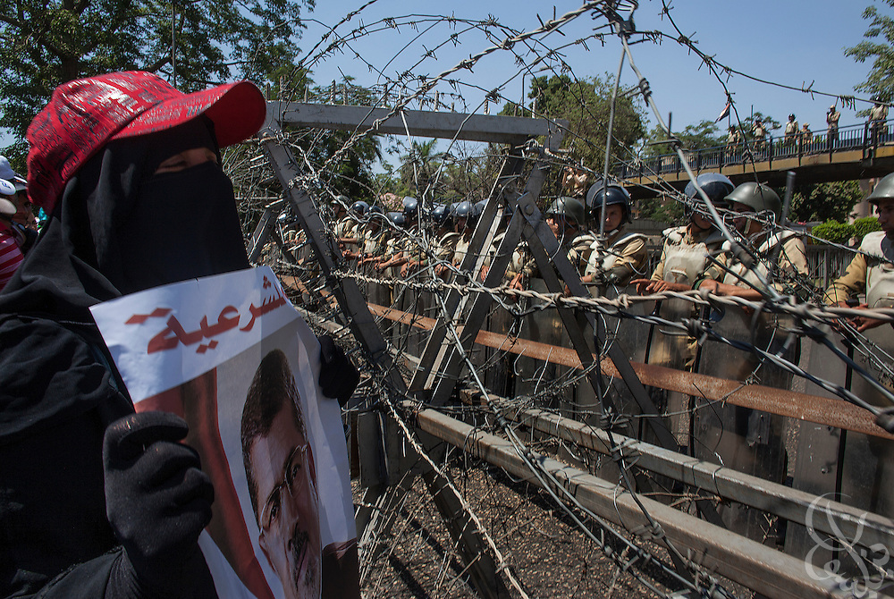 A female Muslim Brotherhood member and supporter of deposed Egyptian president Mohamed Morsi chants pro-Morsi slogans with others at the Egyptian soldiers manning a barbed wire barricade leading to the the Defense Ministry building in the Abbasiya district of Cairo Friday July 30, 2013.  The Muslim Brotherhood has maintained a steady wave of protests and sit-ins for a month since Morsi was deposed by the Egyptian military and replaced by an interim government, and vow to continue until he is reinstated.
