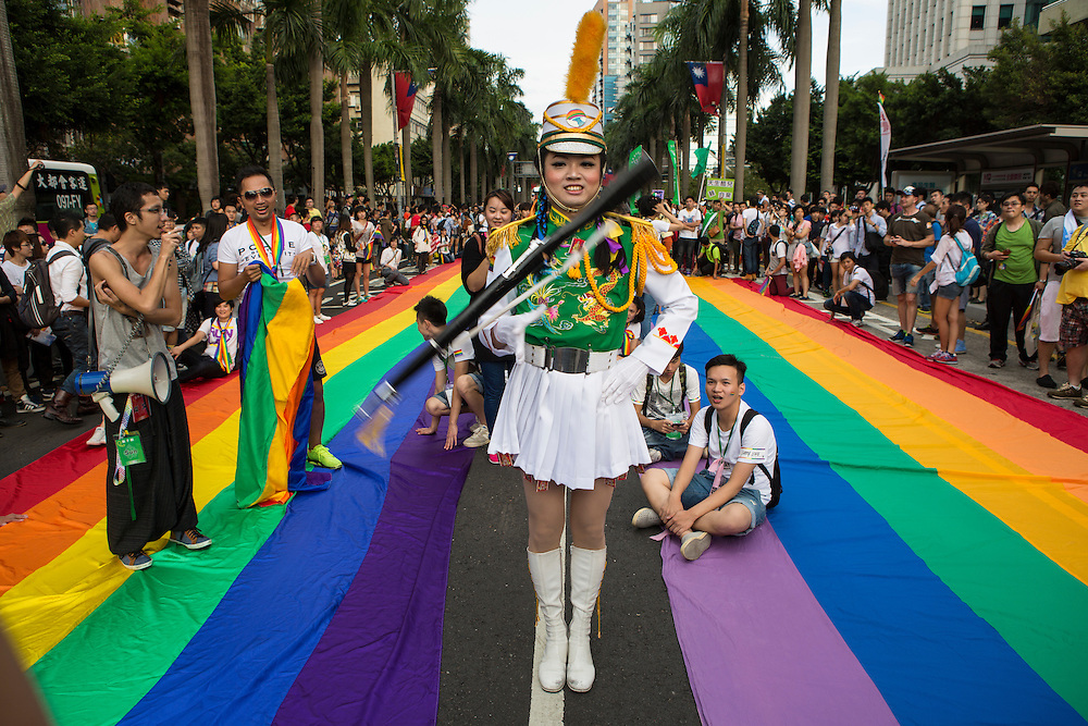 """A color guard with ceremonial rifle performs rifle spinning between two rainbow banners at LGBT Pride. The annual march through Taipei's city streets is the largest in Asia, with well over 50 000 people taking part. The 2014 event had the theme """"Walk in Queer's Shoes"""", to encourage the wider community to lend their support for equal marriage rights."""