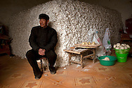 Cotton farmer Yu Feng sits with his stockpile of roughly 3500 kilograms of cotton that he is storing in his home in the town of Huji in the province of Shandong, China, Friday, Jan. 28, 2011. Despite record cotton prices last year, some farmers like Mr. Yu are storing their harvest of cotton and are holding out for even higher prices, hoping to help overcome higher costs of fertilizer and labor, which have both risen 20% in the past year..CREDIT:Keith Bedford for The Wall Street Journal.Slug: COTTON