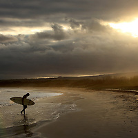 A surfer packed it in for the day as the sun began to set on Isabela island on Galapagos on 6/28/09.