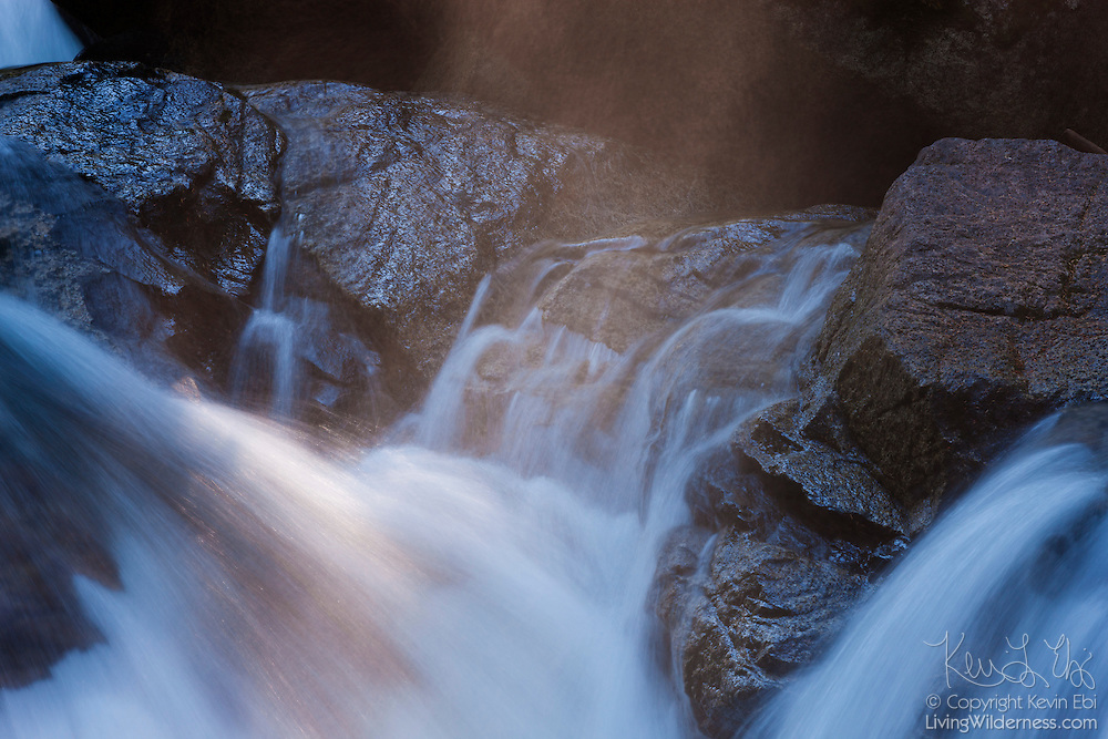 The late afternoon sun highlights the mist rising from a small waterfall in Deception Creek, located near Stevens Pass, Washington.