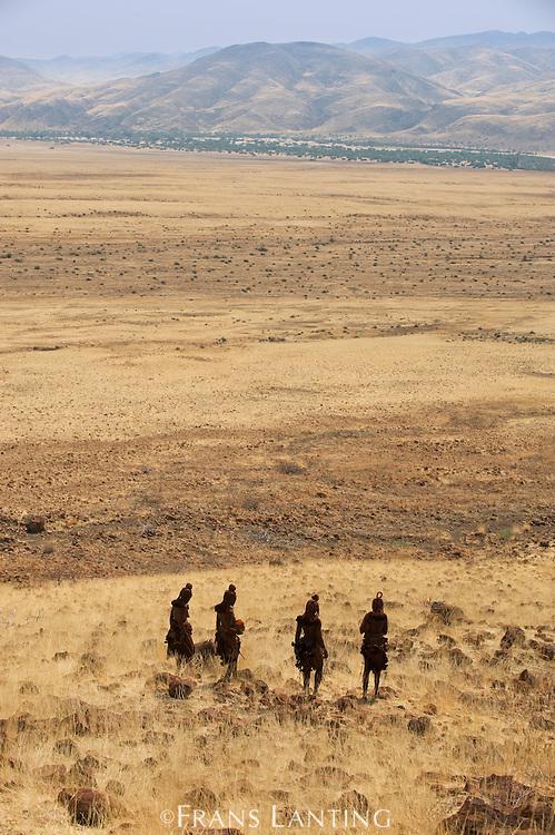 Himba women walking through desert landscape, Puros Conservancy, Damaraland, Namibia