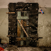 12 of April 2015 / Petrovski/ Donetsk Oblast/ Ukraine - Inside the bunker, main entrance door. A flag of the separatist is hanging on the upright side of the door. A dog on the lower left side intrigued by the newcomers.