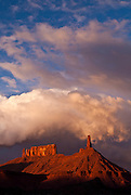Evening light illuminating storm clouds and the sandstone towers known as the Priest, the Nuns, the Rectory and Castleton Tower, in Castle Valley, Utah.