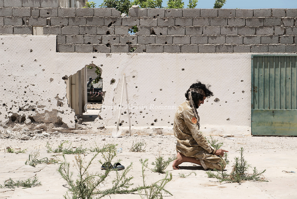 Libya: A Libya's Government of National Accord's (GNA) fighter prays in 700 neighbourhood in Sirte still under ISIS control. Alessio Romenzi