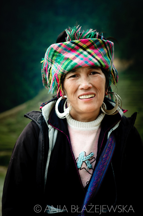 Vietnam, Sapa. Portrait of Hmong woman wearing checkered pattern headdress and traditional earrings.
