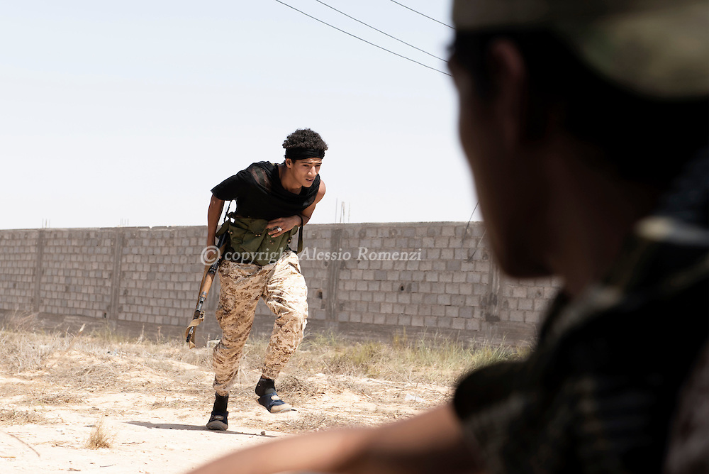 Libya: Fighters sympathising with Libya's Government of National Accord's (GNA) duck on the frontline with ISIS in Sirte. Alessio Romenzi