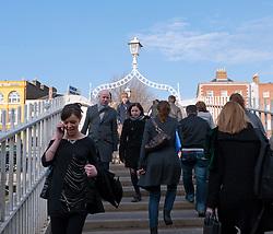 Pedestrians crossing famous Ha'Penny  or Halfpenny Bridge across the River Liffey in Dublin Ireland