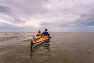 Two paddlers rendezvous under overcast skies in the waters of Florida Bay at the southern end of Everglades National Park. WATERMARKS WILL NOT APPEAR ON PRINTS OR LICENSED IMAGES.