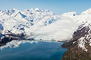 Reflections of Chugach Mountains and tidewater glacier in waters of Prince William Sound in Southcentral Alaska. Spring. Morning.