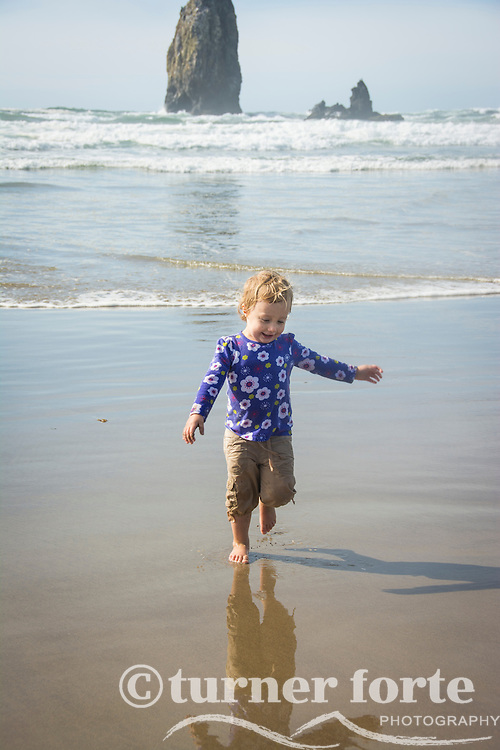 Toddler girl runs from the ocean waves on Cannon Beach, Oregon.