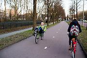 In Utrecht fietst een man op een groene ligfiets over het fietspad bij bedrijventerrein Rijnsweerd.<br /> <br /> In Utrecht a man cycles on a recumbent bike on a bike lane.