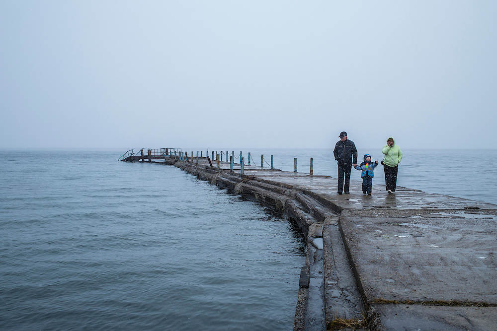 People walk on a pier in Lake Baikal on Saturday, October 26, 2013 in Baikalsk, Russia.