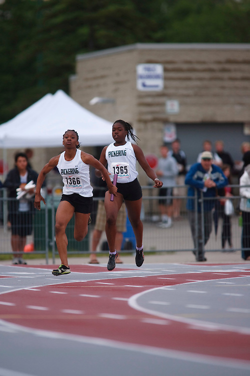 (London, Ontario}---09 June 2010) Maya Daly of Pickering (Ajax)  receives the baton from Kayla Adams during the 4 X 100 meter relay heats at the 2010 OFSAA Ontario High School Track and Field Championships. Photograph copyright GEOFF ROBINS / Mundo Sport Images, 2010.