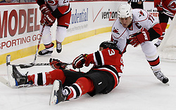 Oct 17, 2009; Newark, NJ, USA; Carolina Hurricanes center Rod Brind'Amour (17) takes down New Jersey Devils right wing David Clarkson (23) during the second period at the Prudential Center.