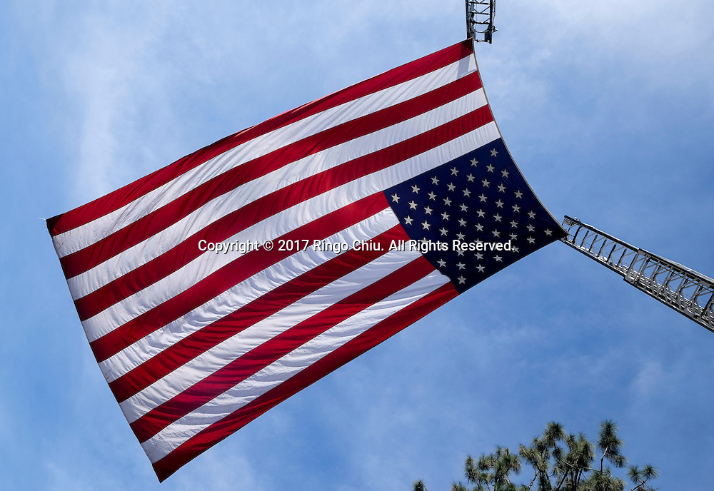 A giant U.S. flag flies over the processional route during the funeral of Whittier Police Officer Keith Boyer at Rose Hills Memorial Park in Whittier, Calif., Friday March 3, 2017. Boyer, who was fatally shot after responding to a traffic crash, was remembered today by thousands of law enforcement officers, friends and family as a dedicated public servant, talented drummer, loving friend and even a ``goofy'' dad.(Photo by Ringo Chiu/PHOTOFORMULA.com)<br />