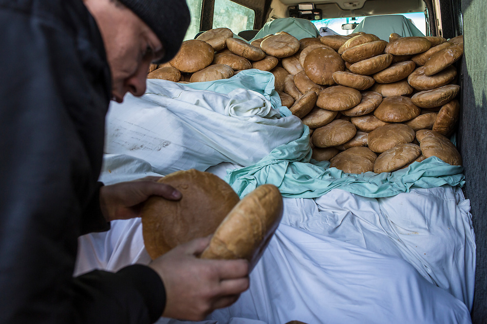 A volunteer from the Good Word Protestant Church delivers bread that will be distributed to local residents in need on Thursday, December 10, 2015 in Mariinka, Ukraine.