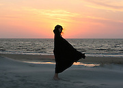 Sunrise at Jekyll Island Georgia beach. Silhouetted woman standing on beach with wind blowing black cape and hair.